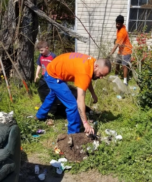 Volunteers from Place of Grace Campus clean up the yard of a nearby home on School Street in East Rockingham on Monday afternoon.