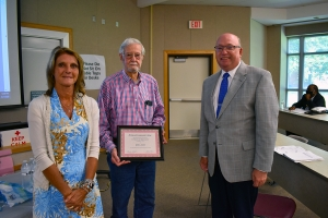 Richmond Community College Board of Trustees Chair Claudia Robinette and Dr. Dale McInnis, College president, present former Trustee Bob Davis with a plaque honoring his service to the College.