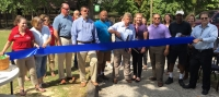 County Commissioner Don Bryant (center) cuts the blue ribbon of East Rockingham Senior Center's new walking trail.