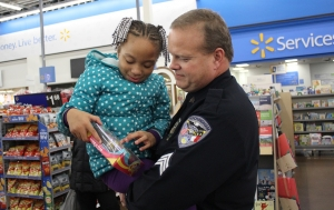 Sgt. Lee Bailey holds 5-year-old Diamond Lemon as she looks at one the presents she picked out during the Rockingham Police Department's annual Shop-With-A-Cop program.
