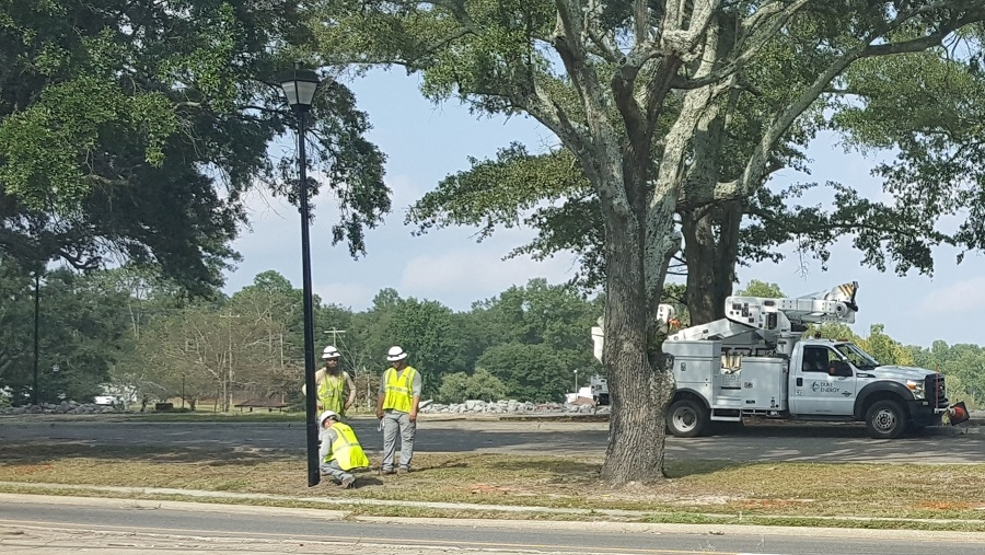 Crews from Duke Energy begin the process of converting the current lighting around Hamlet City Lake to LED lighting on Tuesday.