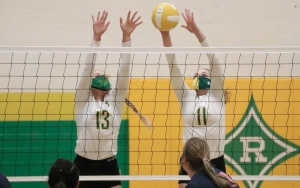 Seniors Shelly Hoffman (13) and Georgia Grace Anderson (11) attempt a block during the second set of Thursday's win.