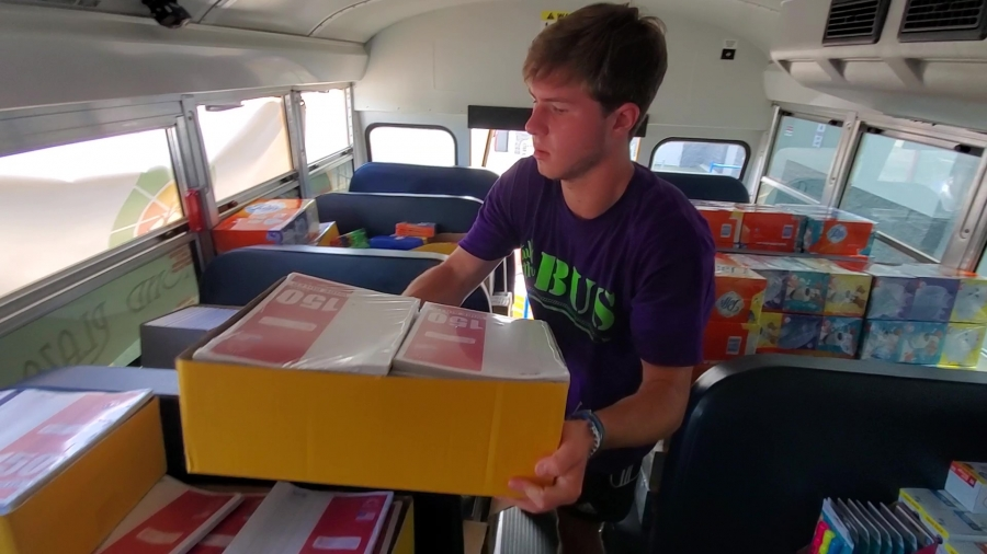 Richmond Senior Beta Club member Noah Jordan stacks a box of notebook paper Thursday during the annual Stuff the Bus campaign.