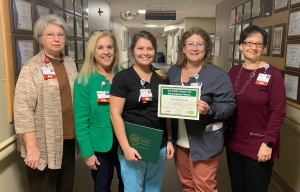 Chelsea Warr, R.N., has been recognized as the December 2018 DAISY Award Winner for FirstHealth of the Carolinas. Chelsea (center in black, holding award) is pictured with (from left to right): Debbie Brand, R.N., clinical practice coordinator; Karen Robeano, DNP, R.N., FirstHealth's chief nursing officer; Betsy Thomas, R.N., BSN, CMSRN, clinical director of the medical neuro intensive care unit at Moore Regional Hospital; and Deana Kerns, R.N., MSN, administrative director of corporate education and professional development. For more information on the DAISY Award, or to nominate a deserving nurse, visit www.firsthealth.org/daisy.