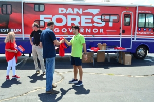 Republican candidate for the Richmond County Board of Commissioners Andy Grooms receives a Dan Forest T-shirt during a stop in Rockingham by the gubernatorial candidate's campaign bus.