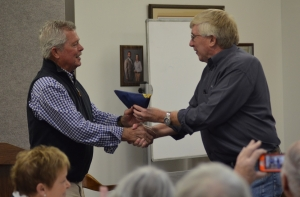 Jim Lambeth, of Triple L Farms, accepts a state flag from Sen. Tom McInnis after being named Farm of the Year during the annual Farmers Luncheon.