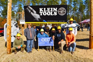 CED sales representative Rita Clewis stands with students in the fourth Electric Lineman program and the coordinator for the program, Scott Caulder.
