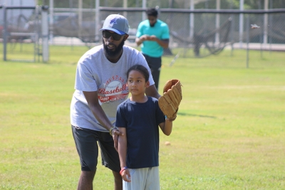 Anthony Hailey helps a camper work on glove-side turns during Saturday's All S.T.A.R. Academy baseball training camp.
