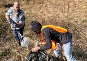 von Drehle employees Jason Fulp and Will Brown pick up trash Thursday morning near the Hitchcock Creek bridge in Cordova.
