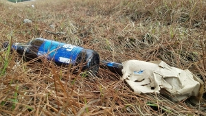 Two beer bottles are among the many scattered alongside Mizpah Road, highlighting the county's littering problem.