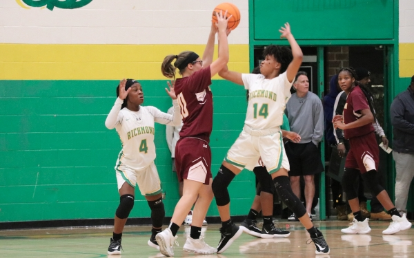 Jayla McDougald (4) and Keionna Love (14) apply defensive pressure on Jaylen Carter in Friday's rout of Lumberton.