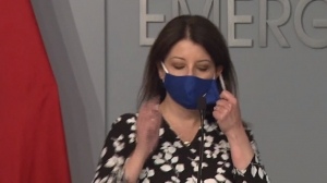 Health and Human Services Secretary Dr. Mandy Cohen takes off a face mask to speak during Monday's briefing. Gov. Roy Cooper said state health officials are considering making mask-wearing mandatory.