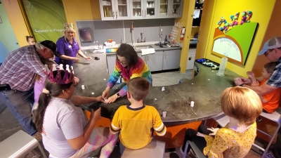 Melissa Staub helps kids with their Alka-Seltzer bottle Rockets during the final science show for Discovery Place Kids' 7th birthday celebration on Sunday.
