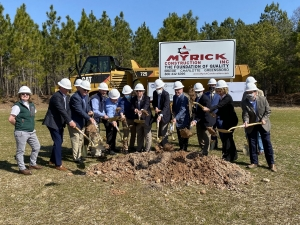State and local dignitaries and representatives of Global Packaging ceremonially toss dirt in the air during a groundbreaking ceremony for the company's future plant.