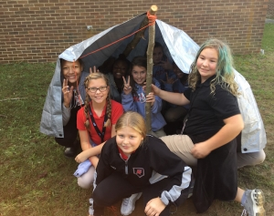 "Several sixth grade students at Hamlet Middle School show off the shelter they built during a recent STEAM activity on the novel ""Hatchet""."