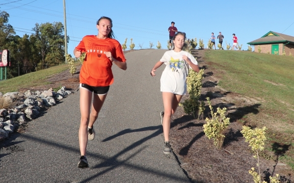 Junior Maylyn Wallace (left) and sophomore Rylie Bohman (right) run a lap around campus on Tuesday.