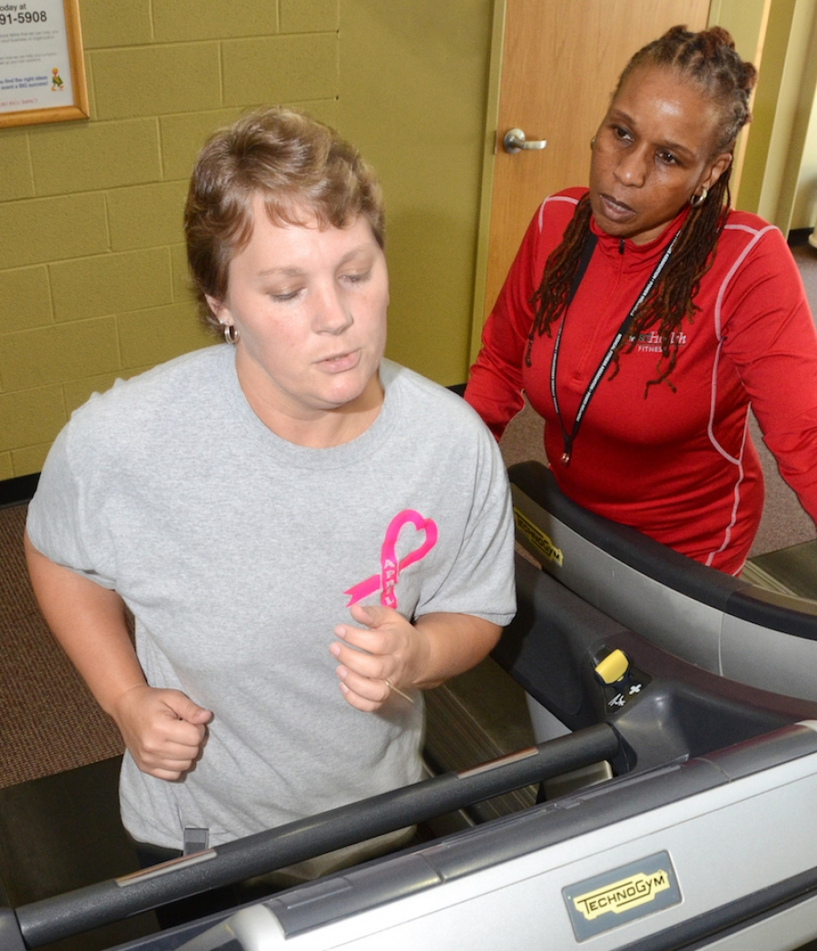 Cinnamon LeBlanc, manager of FirstHealth Fitness-Southern Pines, checks April Stewart's treadmill walk/run time during a recent training session for the 1in8K Run for Moore. A breast cancer survivor, Stewart will fulfill a longtime personal goal when she joins other survivors and supporters in the Oct. 7 race through the Village of Pinehurst.