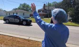 An employee of FirstHealth Moore Regional Hospital-Richmond waves as a passing deputy offers thanks during a parade in April.