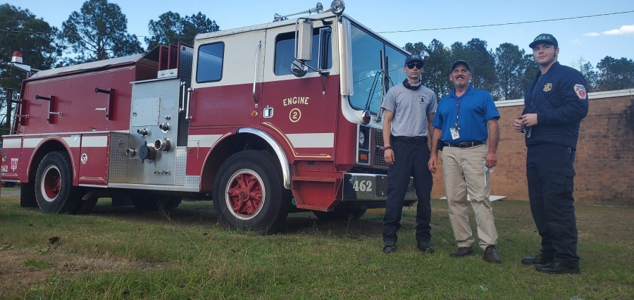 Instructor Vic McCaskill stands flanked by Zac Sharpe, left, and Kendell Watson. Sharpe was hired by the Aberdeen Fire Department in June, just before graduation and Watson is currently an intern with the department.