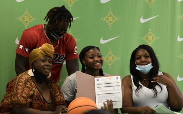 Senior Davionna Campebell smiles as she holds up her signed letter of commitment to Johnston Community College.