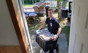 Jessie Broadwater, junior member of the Richmond County Rescue Squad, helps unload barbecue from an ambulance for the squad's annual plate sale.