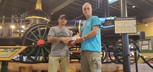 Seaboard Festival 5k Race Director Duke Smith receives a $500 check from Donald Dees of Dees Bees Apiary. The donation will go toward a scholarship.