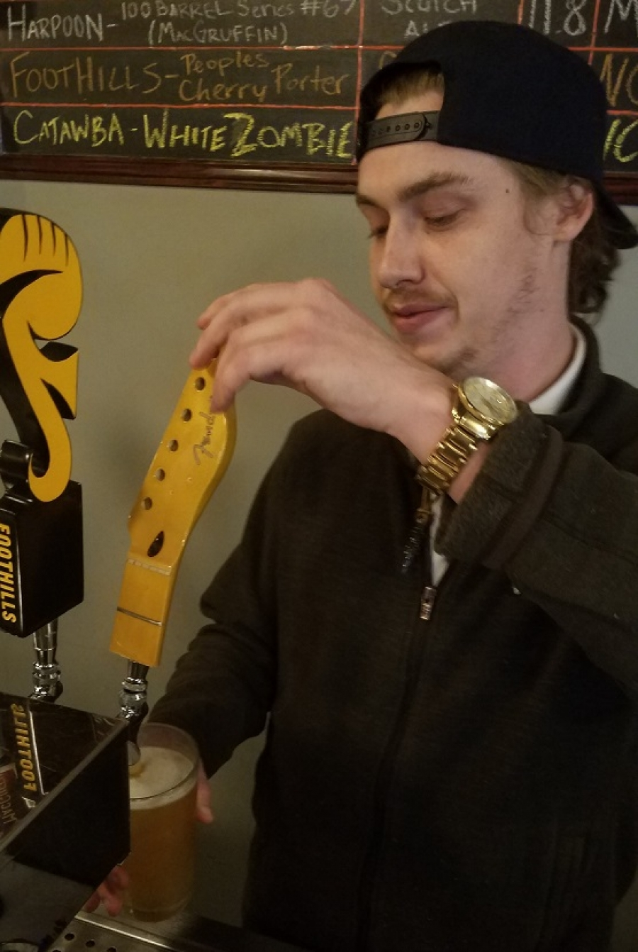 A bartender at The Bruin Craft Beer and Wine in New Bern pours a glass of White Zombie, a white ale made by Charlotte-based Catawba Brewing Company.