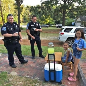 Hamlet Police officers Patrolman Donald Morton and Sgt. Britt Emert stop by a local lemonade stand May 25.