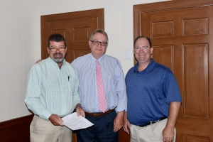 County Manager Bryan Land, Attorney Bill Webb, and Rev. Gary Richardson complete property transfer