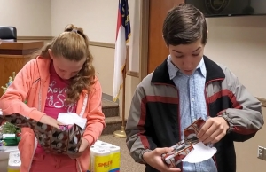 Siblings Zarya Rardin and Dasan Boone each open one of their gifts from the Hamlet Police Department, Water Department and City Hall on Monday. See a video at the bottom of this post.