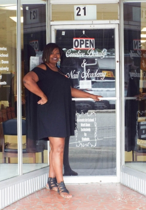 Chanda Jenkins, owner of Creative Beauty and Nail Academy, poses in front of her school's Hamlet location.