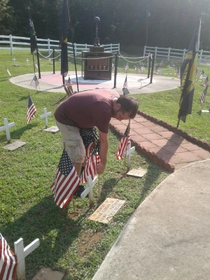Donny Sweatt, a member of the VFW Post 4203 Auxiliary, places flags at Veterans Memorial Park on Thursday in preparation for Saturday's service.