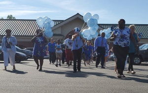 A crowd of law enforcement officers, social workers and foster parents walk from the Richmond County Department of Social Services to Harrington Square on Tuesday to recognize April as Child Abuse Prevention Month.