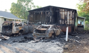 The charred remains of two vehicles linger following a Friday morning fire in East Rockingham.