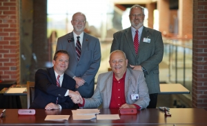 Dr. William M. Downs, president of Gardner-Webb University, and Kevin Parsons, vice president of instruction for Richmond Community College, shake hands after signing the Bulldog Bound co-admission agreement. Standing in back, from left, are Dr. Ben Leslie, provost and executive vice president for Gardner Webb, and Brent Barbee, executive vice president/CFO for RichmondCC.
