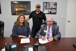 Lori Benn, Quality and Continual Improvement manager for Metallix, sits with Dr. Dale McInnis, president of Richmond Community College, while he signs the contract to enter a partnership for customized training for the company. Standing behind them is Kevin Grimsley, production manager in Maxton.