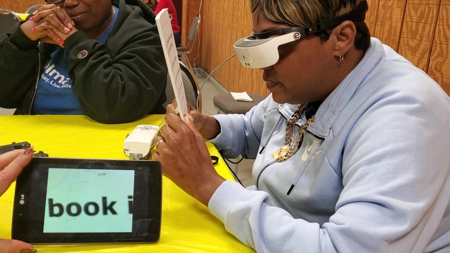 A tablet shows exactly what Rinika Pittman is looking at as she reads for the first time since 2014 using eSight glasses during an evaluation at the Hamlet Lions Club on Monday.