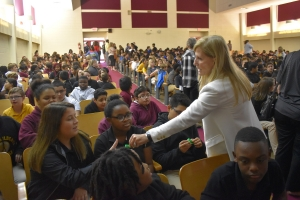 Debbie Dalton passes out bright green wristbands to students as a reminder to make good decisions and cherish life.