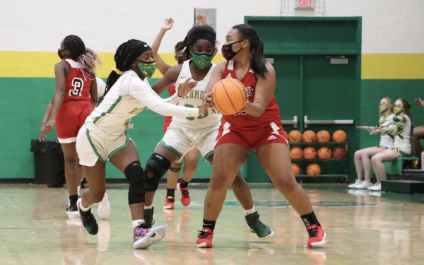 Jayla McDougald (left) and Allyiah Swiney strip the ball from Kyanna Hollingsworth (20) in Friday's win.