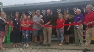 Will Moss (black shirt) is joined by longtime employee Mike Long to cut the ceremonial ribbon for the grand re-opening of Moss Brothers Tire late Thursday morning. Moss is the fourth-generation owner of the business and Long has been with the company more than 30 years.