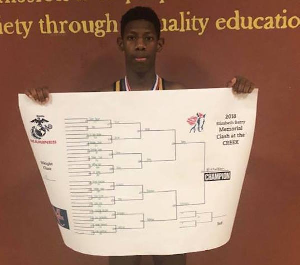 Junior Joseph Nicholson poses with his championship bracket after winning the 11-3 pound title at Mallard Creek High School.