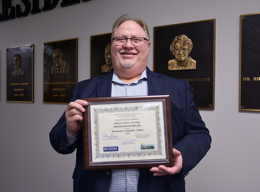 Richmond Community College Small Business Center Director Butch Farrah holds the award that the College received for Innovative Programs and Seminars from the North Carolina Community College System's Small Business Center Network.