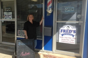 Angela Butler, owner of Fred's Barber Shop in Hamlet, poses in front of her shop.
