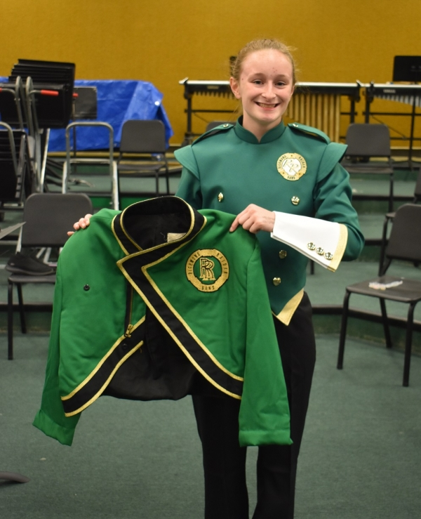 Senior and mellophone section leader Gabrielle Bellanger holds the old uniform jacket next to the new uniform to compare the two.