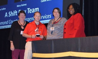 Mary Gainey, Calvin Smith and Christine Collins receive an award in October for their outstanding work.