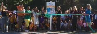 "Dr. Kate Smith (center) prepares to cut the ribbon of Mineral Springs Elementary's new ""Daily Mile"" trail."
