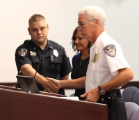 Rockingham Police Chief Billy Kelly (right) shakes the hand of Detective Ronald Brigman (left) during his recognition by City Council Tuesday.