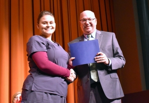 Nursing Assistant student Amy Wilkins accepts her certificate of completion from Dr. Dale McInnis, president of Richmond Community College. Wilkins was the guest speaker for the Nursing Assistant Pinning Ceremony on Wednesday.