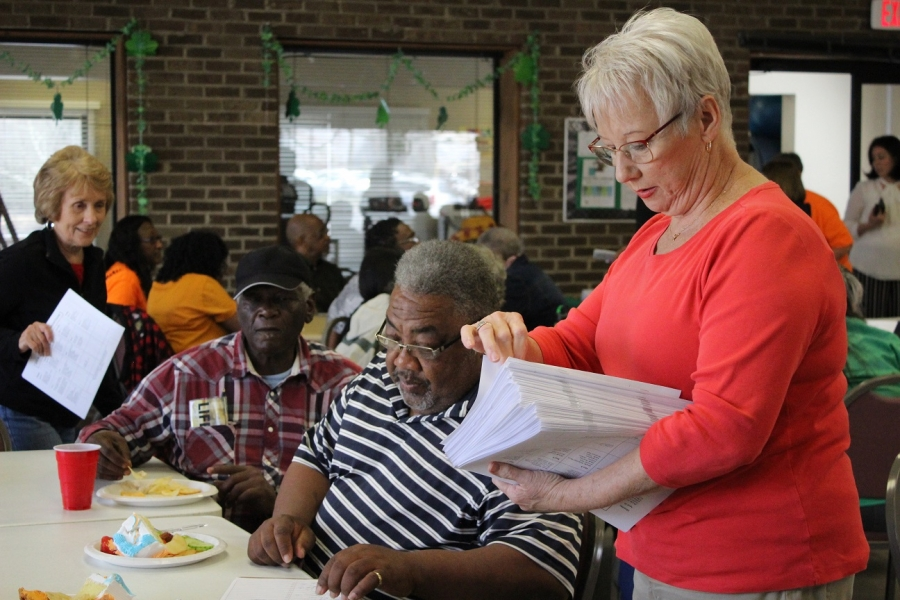 Susan Sellers, coordinator of the Richmond County Silver Arts, passes out information packets during Thursday's Senior Games kick-off.