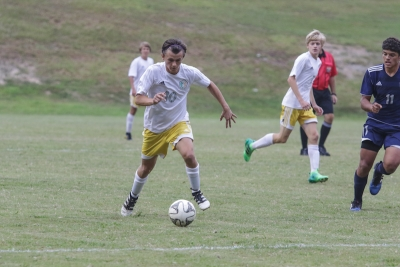 Senior forward Brett Baucom slides past Purnell Swett's Jydor Locklear to earn his first goal of the season.